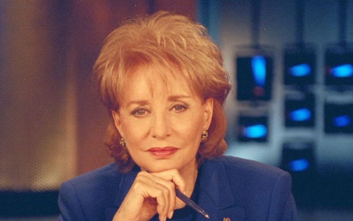 Barbara Walters in a blue coat poses a picture at the studio.