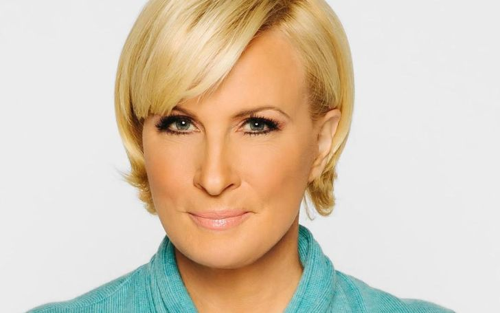 Mika Brzezinski in a blue dress poses for a picture.