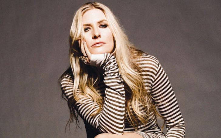 Holly Williams in a brown dress poses for a picture.