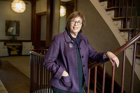 Linda Greenhouse in a purple coat poses for a picture.