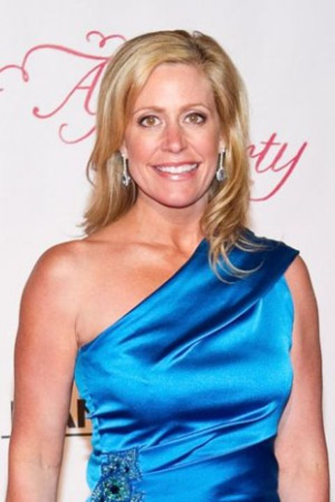 Melissa Francis in a blue dress poses for a picture.