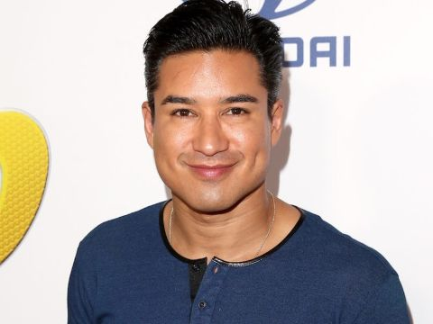 Mario Lopez in a blue t-shirt poses for a picture.