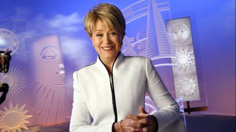 Jane Pauley in a white dress poses for a picture