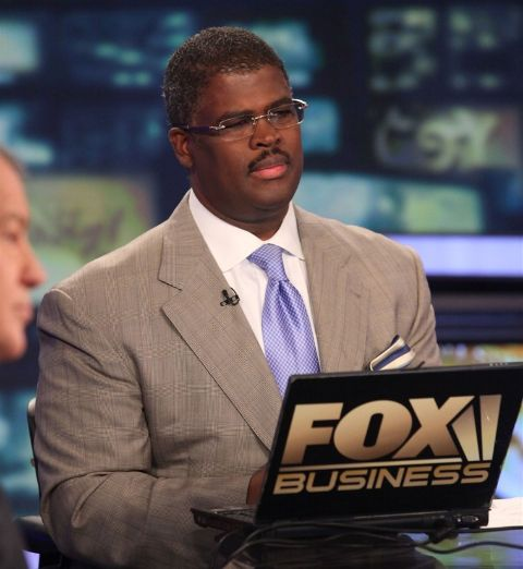 Charles Payne in a grey suit poses for a picture.