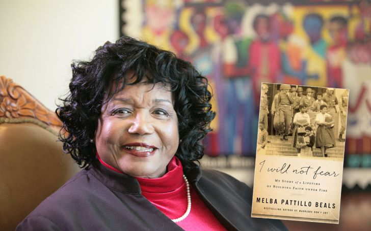 Melba Pattillo Beals in a black coat poses for a picture.