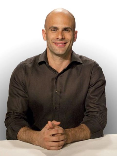 Sam Kass in a brown shirt poses for a picture.