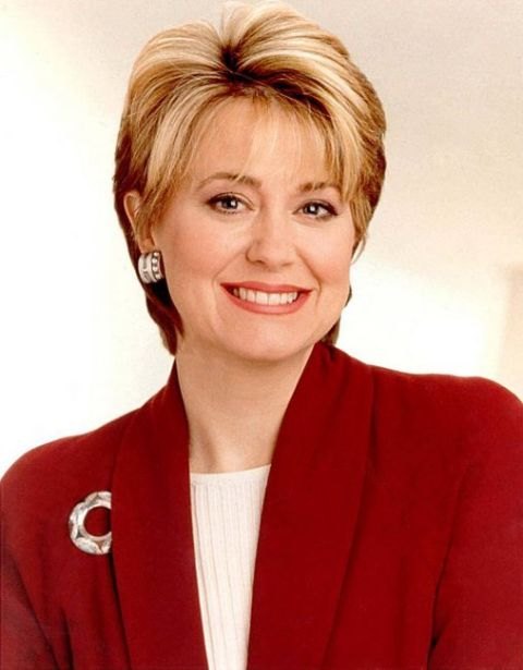 Jane Pauley in a red coat smiles at the camera.