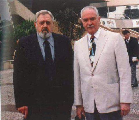 Robert Benevides  in black suit poses with late actor Raymond Burr.