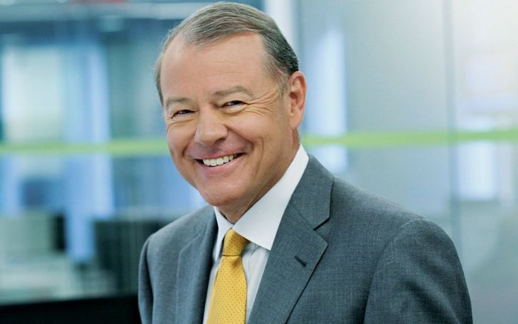 Stuart Varney in a grey suit poses for a picture.