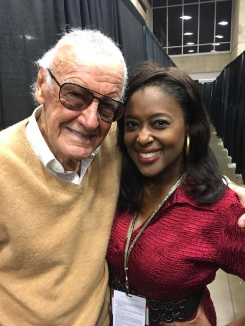 Sharron Melton in red poses a picture with Stan Lee.
