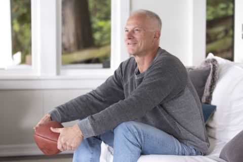 Kenny Mayne in a grey t-shirt poses for a picture at his couch.