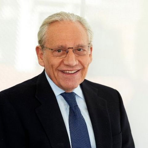 Bob Woodward in a black suit poses for a picture.