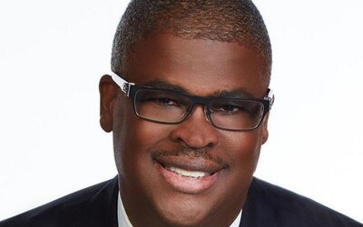 Charles Payne in a black suit poses for a picture.