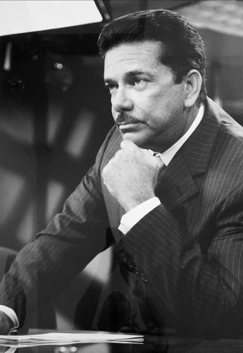 Ramon Enrique Torres in a black suit poses a picture.