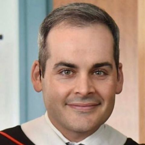 David Begnaud in a black suit poses for a picture.