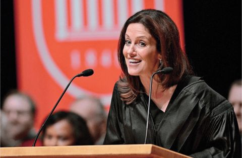Sharyn Alfonsi in a black jacket delivering a speech.