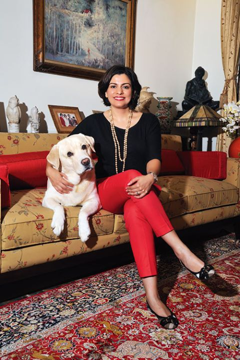 Nidhi Razdan in a black dress poses with her dog.