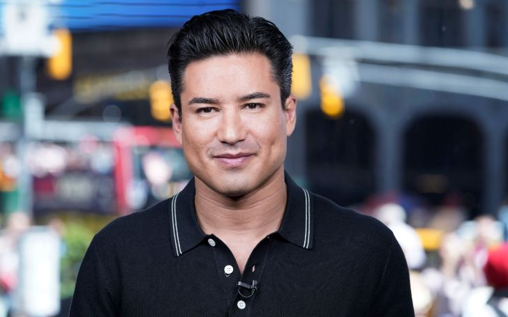 Mario Lopez in a black t-shirt poses for a picture.