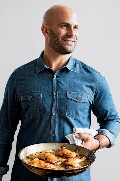 Sam Kass poses a picture in a blue shirt.