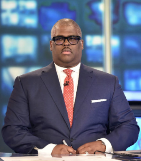 Charles Payne in a blue suit poses for a picture.