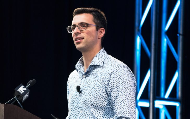 Ezra Klein in a blue shirt caught in the camera.