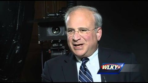 Richard Schlesinger in a black suit giving an interview.