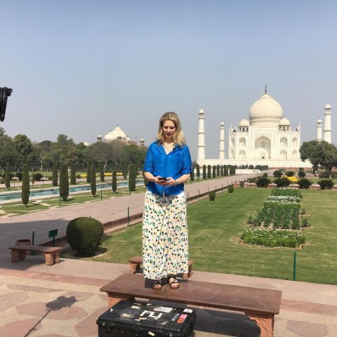 Abigail Bimman in a blue t-shirt poses for a picture at Taj Mahal.
