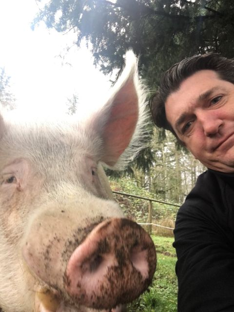 Aaron McArthur poses  a picture with a pig.