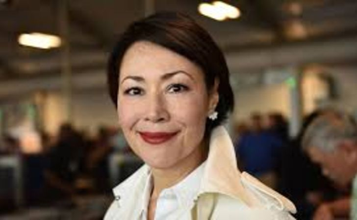 Ann Curry in a white dress poses for a picture.