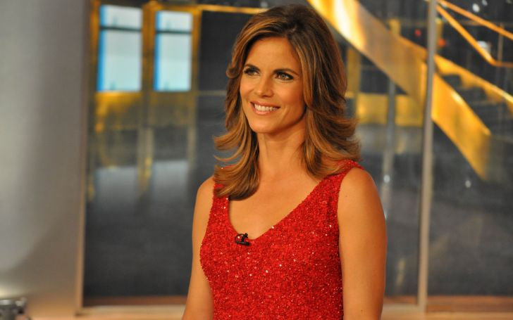 Natalie Morales in a red dress poses for a picture.
