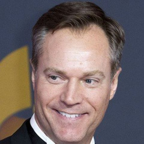Chris Gailus in a black suit smiling at the camera