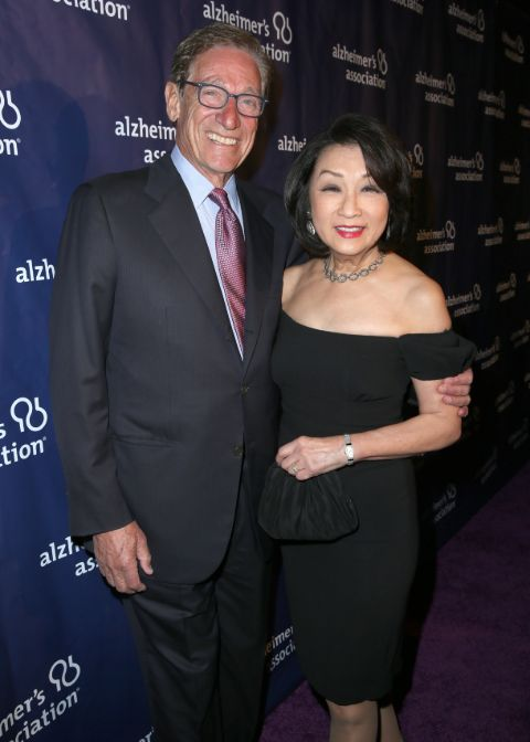 Connie Chung in a black dress poses with husband Maury Povich.