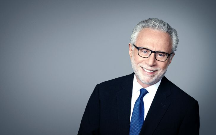 Wolf Blitzer in a black suit poses for a picturee.