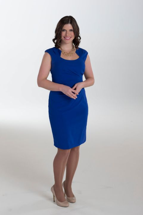 Kaitlyn Herbst in a blue dress poses for a picture.