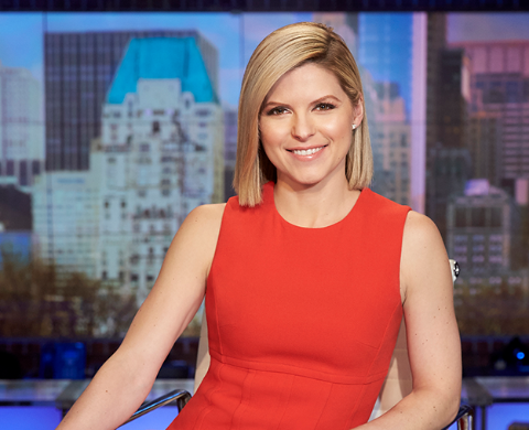 Kate Bolduan in a red dress poses for a picture.