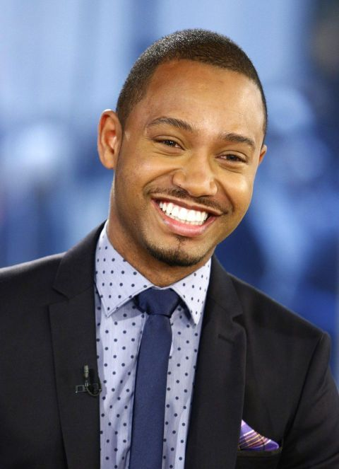 Terrence J in a black suit smiles at the camera.