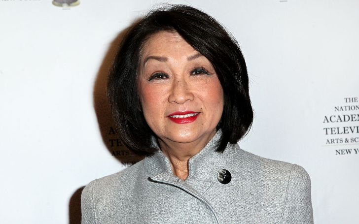 Connie Chung in a white coat poses for a picture.