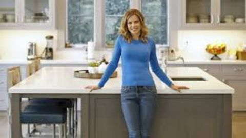 Natalie Morales in a blue t-shirt poses for a picture.