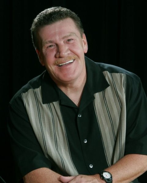Mike Armstrong in a black shirt poses for a picture.