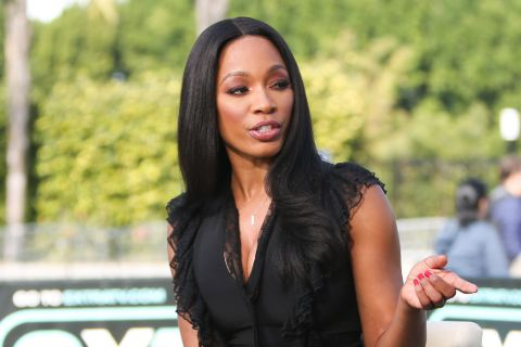 Cari Champion in a black dress poses for a picture.