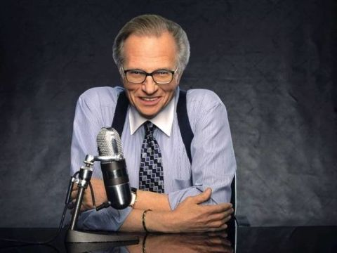 Larry King poses for a picture in a white shirt.
