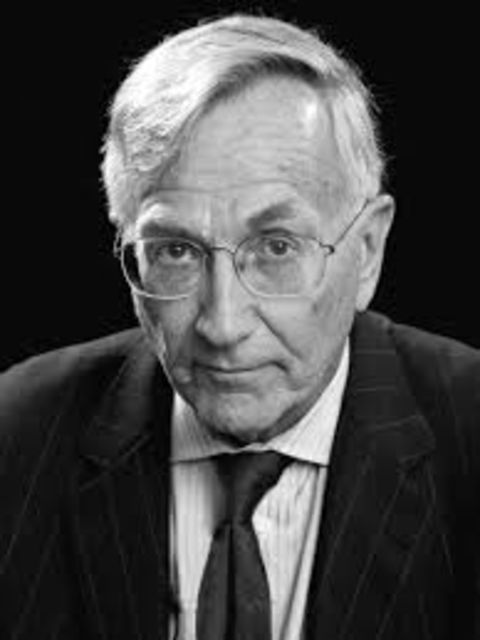 Seymour Hersh in a black suit poses for a picture.