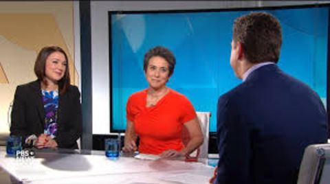 Amy Walter in a red t-shirt caught in the camera during a program.