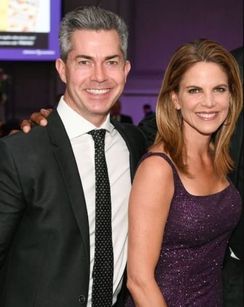 Natalie Morales in a purple dress with husband Joe Rhodes.