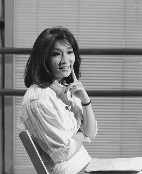 Connie Chung in a white dress poses for a picture.
