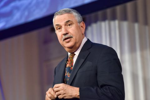 Thomas Friedman in a black suit poses for a picture.