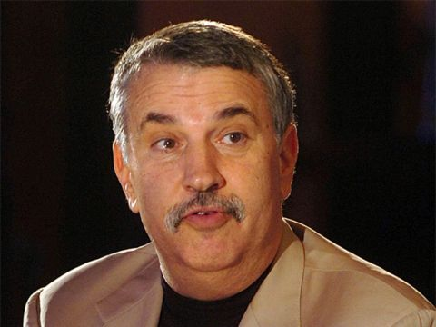 Thomas Friedman in a brown coat poses for a picture.