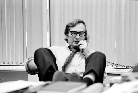 Seymour Hersh in a white shirt talking on a phone call.