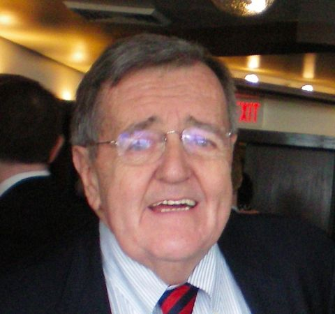 Mark Shields in a black suit poses for a picture.
