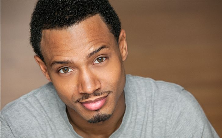 Terrence J in a grey t-shirt poses for a picture.